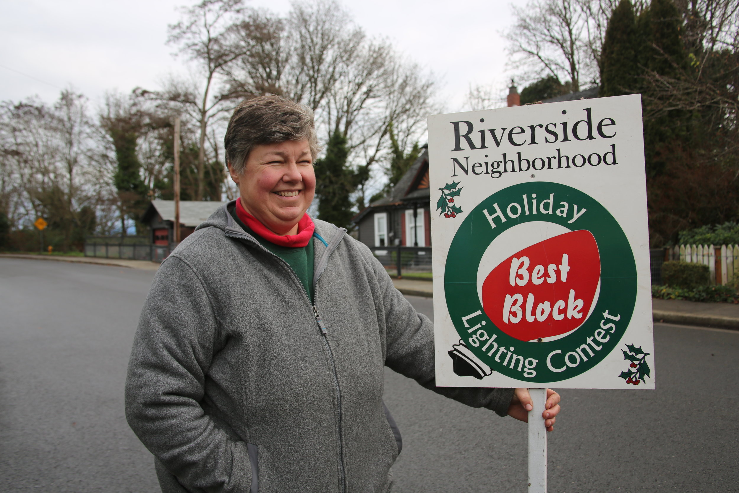 Katrina holding the returned Riverside neighborhood Holiday Lighting Contest sign.