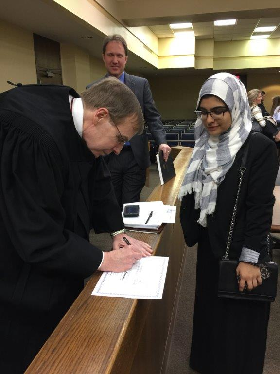 "Justice Edmunds signing a ""Best Advocate"" award for competitor at N.C. Advocates for Justice High School Mock Trial Competition."
