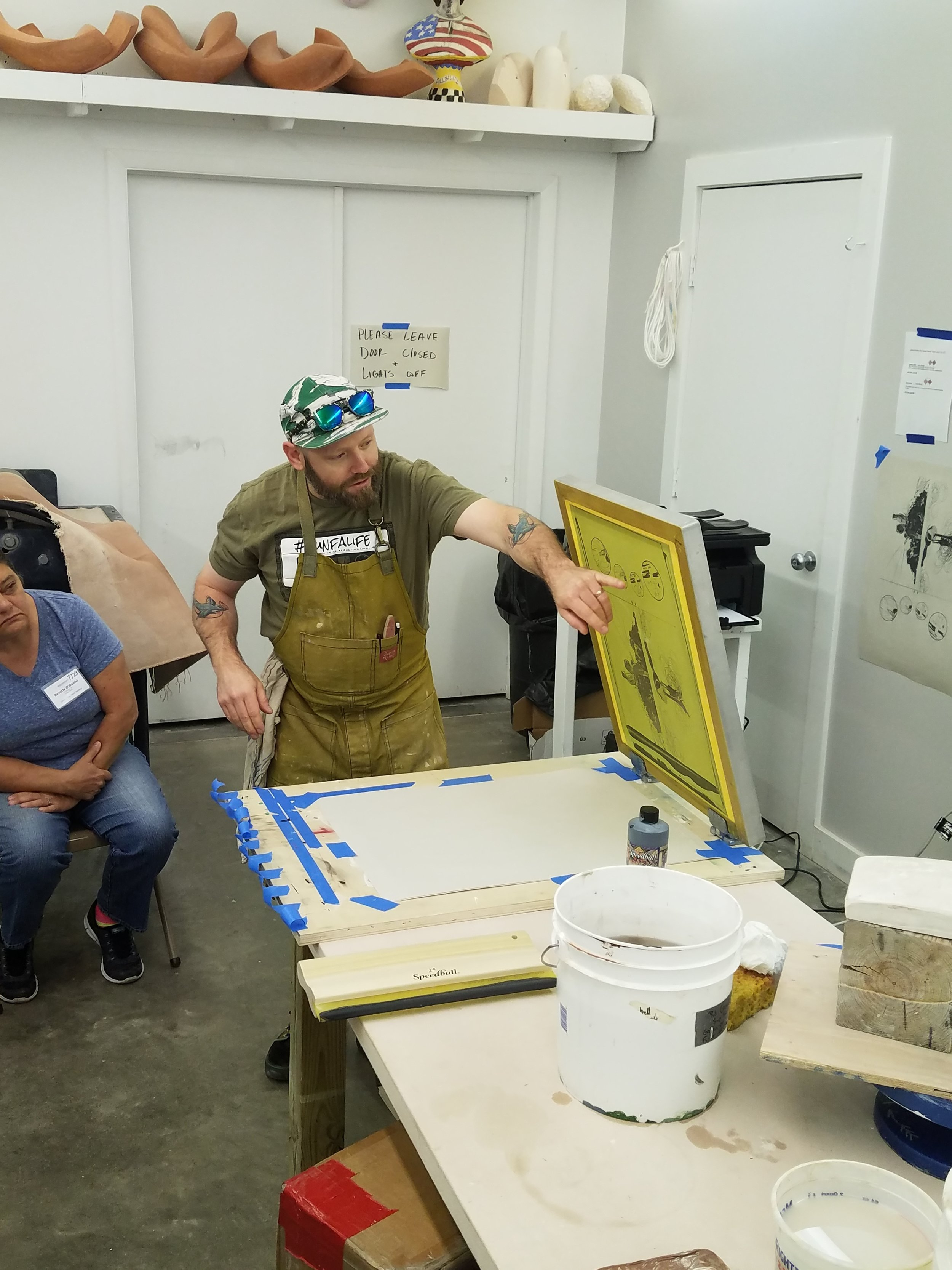 Israel is giving a demo on how to screen print onto newsprint with underglaze for a newprint transfer.