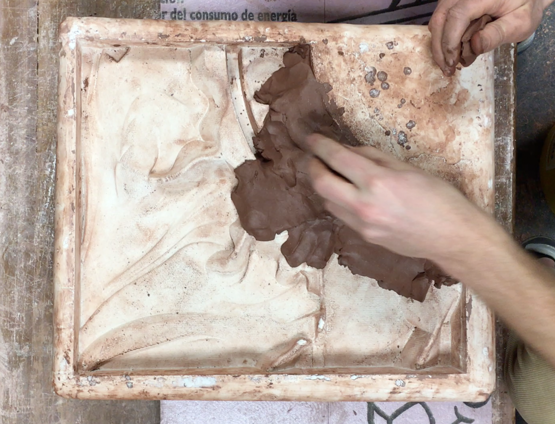 Students pressing clay into the molds