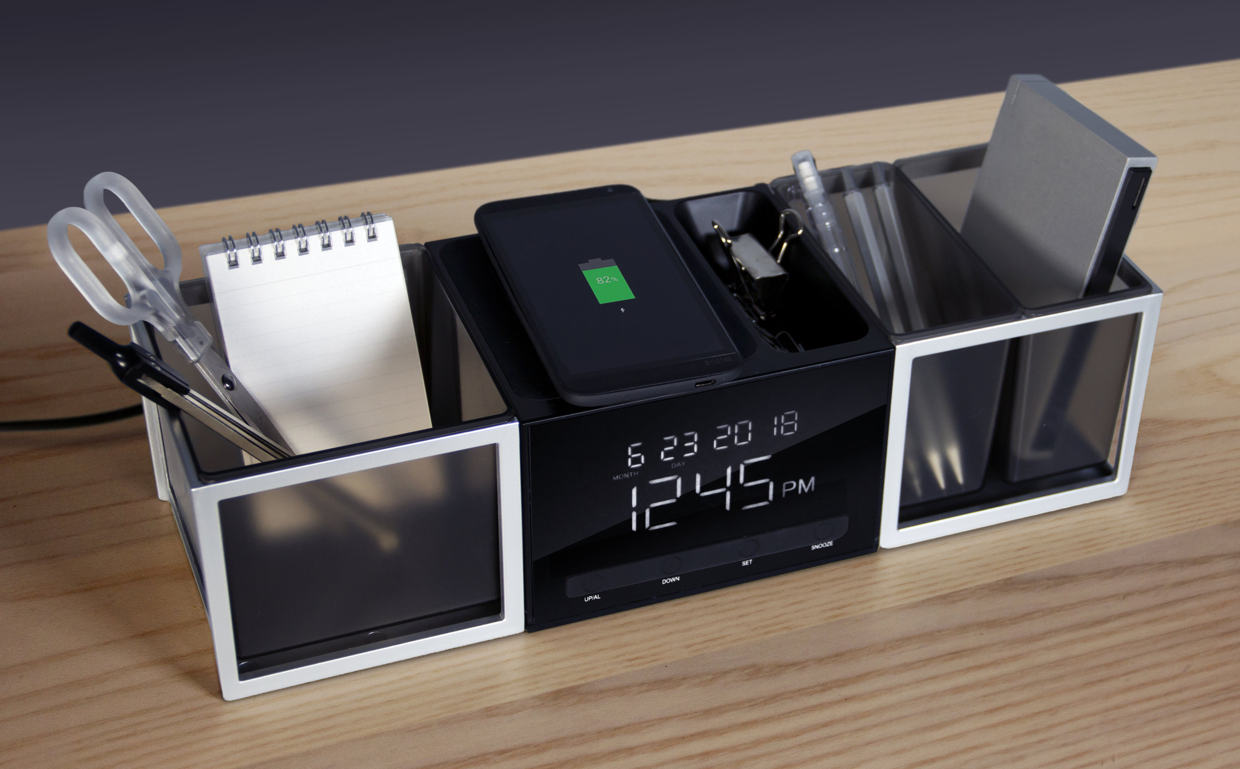 ExecConnect desktop organizer - June 2018   Exec Connect incorporates a set of USB connectors and also a wireless charging pad, combined with a digital alarm clock/calendar and a number of interchangeable storage caddies. The linear design of the unit takes inspiration form mid-century architecture and the combined use of solid forms, framing, and transparency to create a sense of lightness and visual focus.