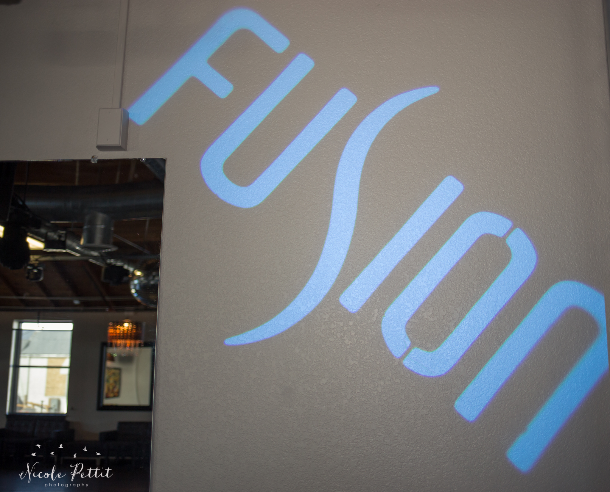 Fusion Nightclub logo projected on the wall at Fusion Nightclub in Fort Collins, Colorado