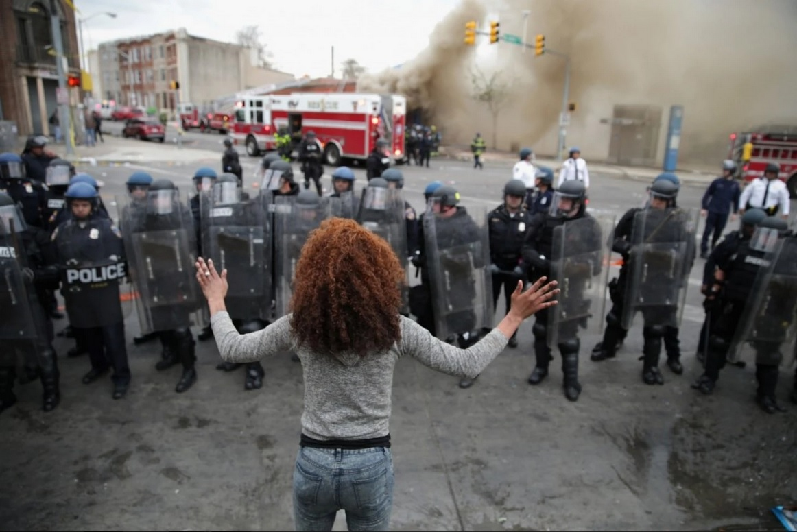 A woman faces down a line of Baltimore police officers in riot gear on Monday during protests after the funeral of Freddie Gray. Courtesy of The Washington Post.