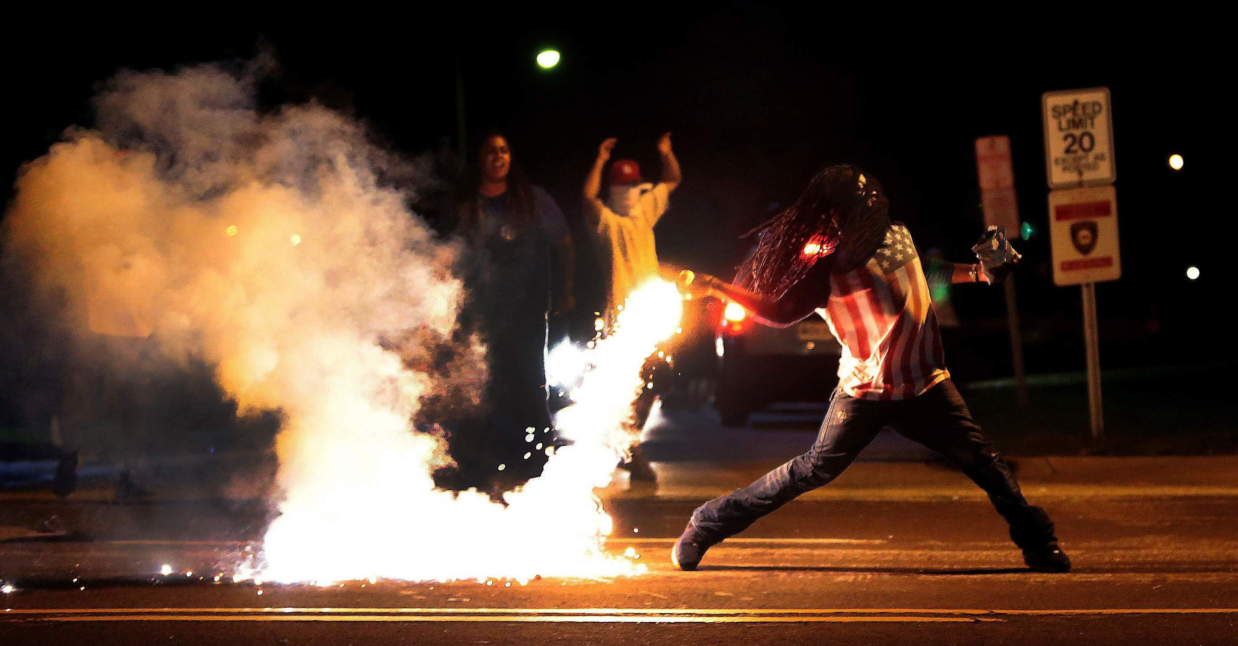 A protester in Fergusonthrowingback a can of tear gas deployed by police during a peaceful demonstration. Photo:Associated Press