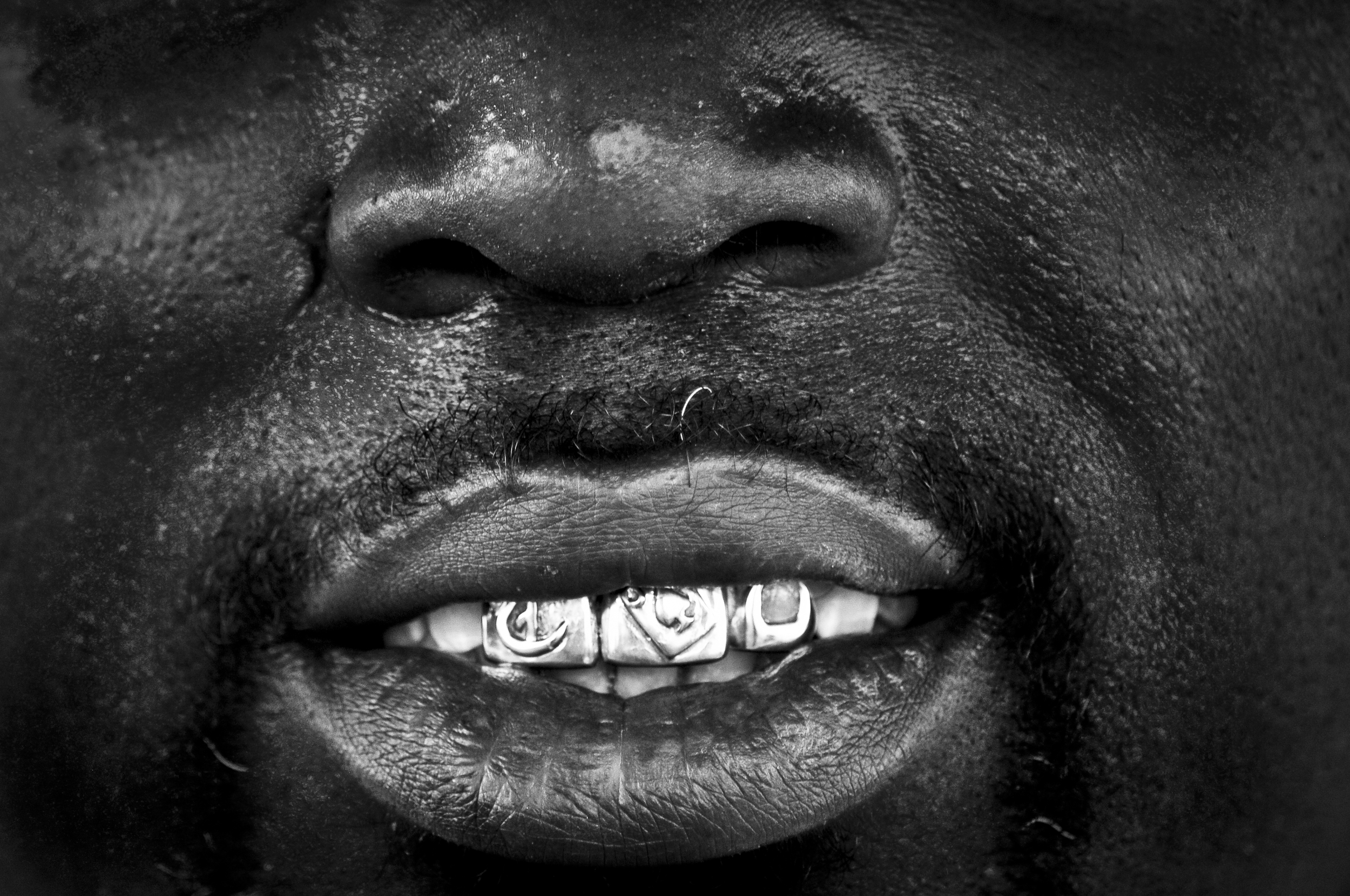 Tyrone Jackson shows off his gold teeth outside of his business North Side Audio in North Tulsa. Many of the small businesses in North Tulsa struggle to stay open due to the violence and poverty that plagues the area. Nick Oxford for The New York Times