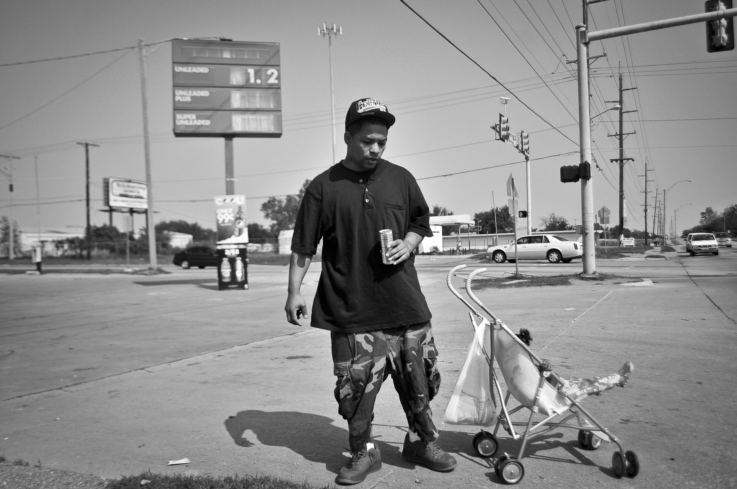 Carl Moore stands along N. Peoria Ave. with his daughter in North Tulsa. Moore came to Tulsa from Houston to escape the problems plaguing the neighborhood he was living in. Nick Oxford for The New York Times