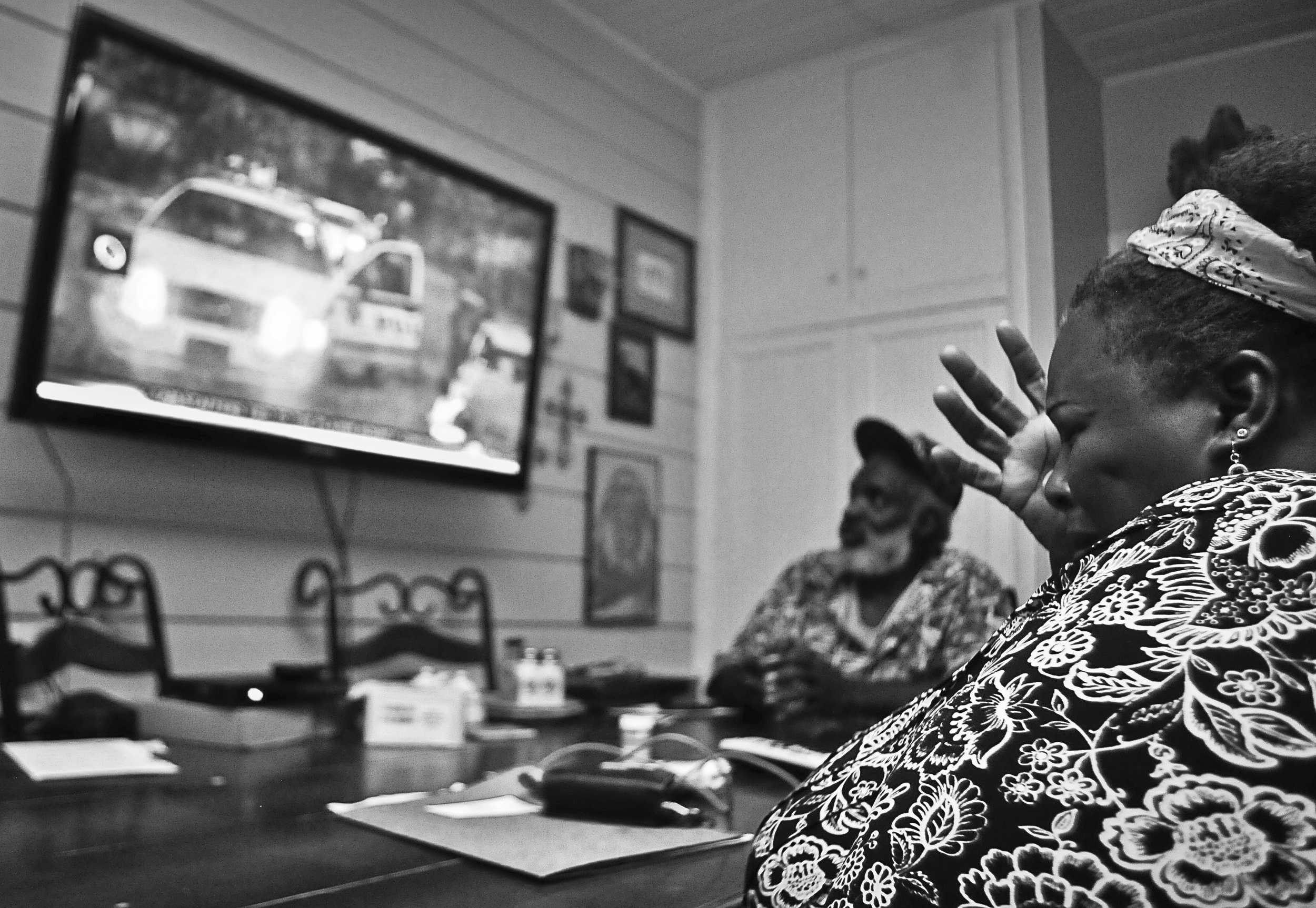 Tonya Clardy, the sister in law of shooting victim Bobby Clark, gets emotional while watching a special report about the shootings in Tonya's home on Sunday evening. Nick Oxford for The New York Times