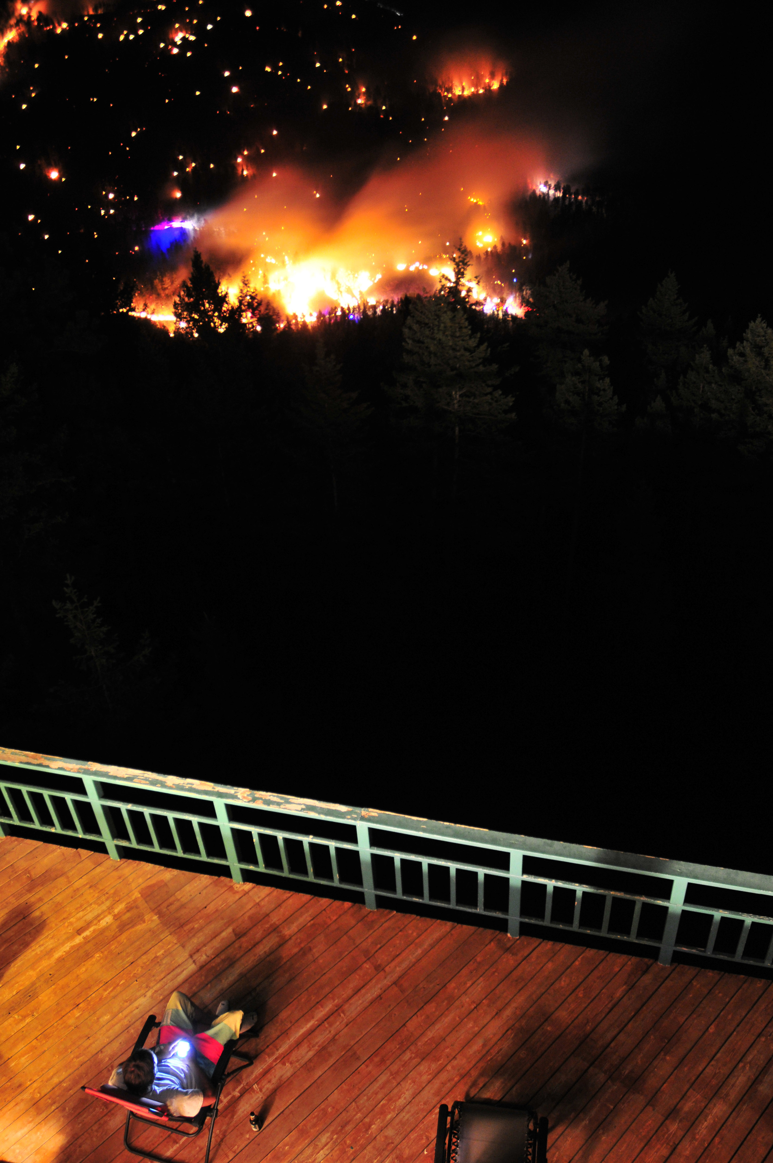 Patrick Gillean watches the Maxwell Fire burn from his patio in Boulder Colorado June 26, 2011. The Maxwell Fire burned approximately seventy acres of public forest in Lefthand Canyon before firefighters could control the blaze.