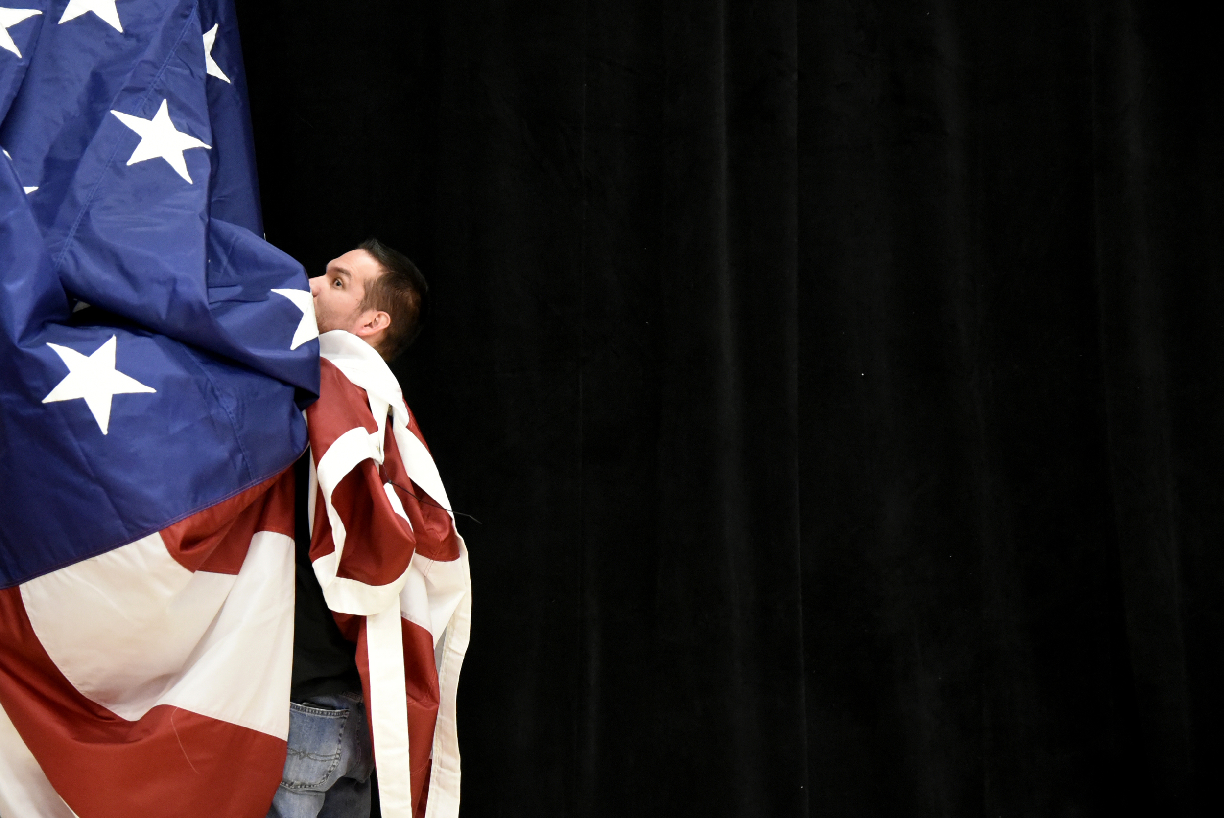 A campaign volunteer takes down the American flag after a rally for Republican presidential candidate Marco Rubio in Oklahoma City on the eve of Super Tuesday.