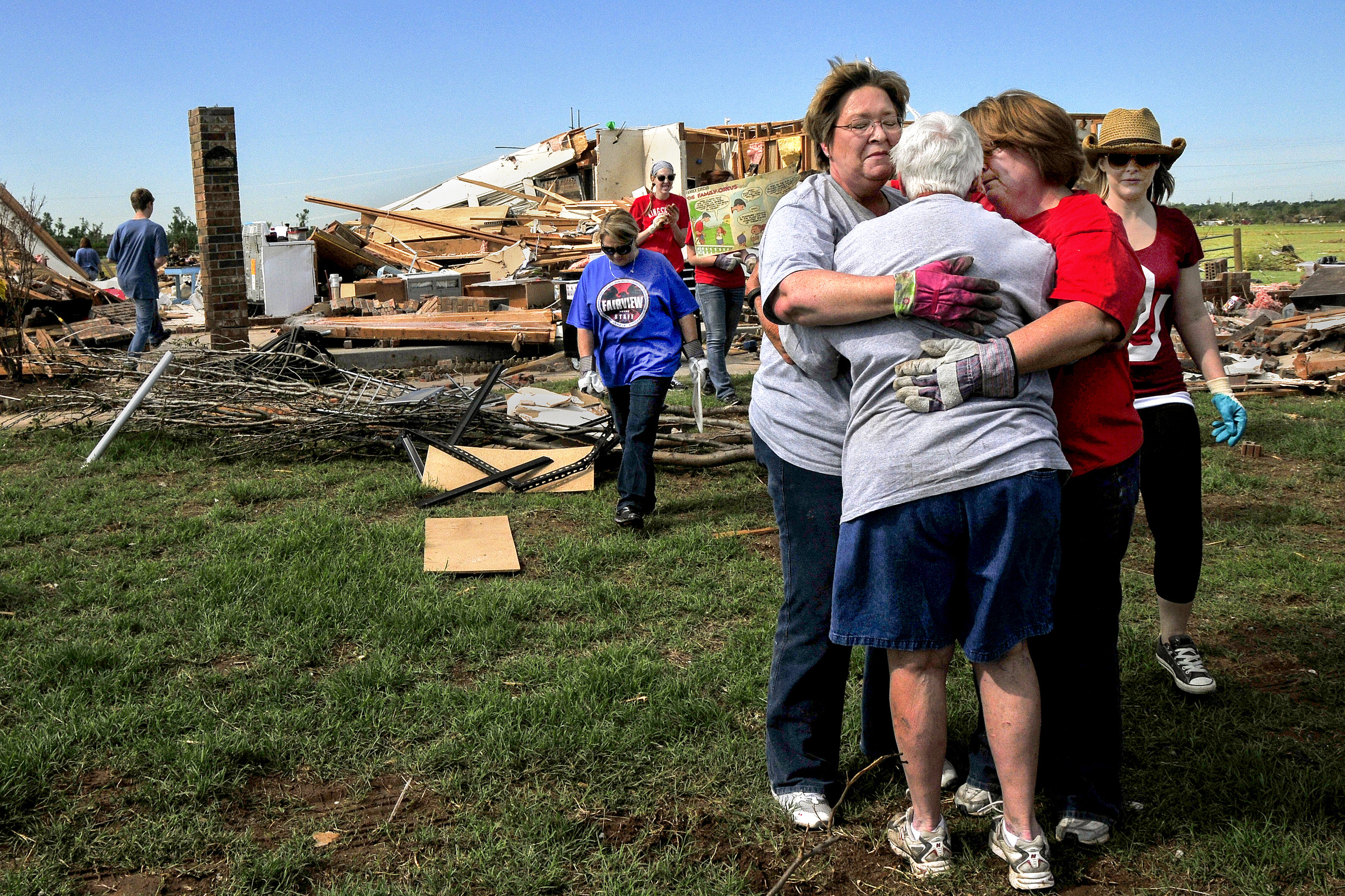 Teachers from Fairview Elementary school embrace former school counselor Kay Johnson, center, in front of her home in a neighborhood that was in the direct path of Mondays Tornado on Wednesday May, 22 in South Oklahoma City just west of Moore. The path that the tornado took through this neighborhood was almost exactly the same as on May 3rd 1999. 3120 sw 153rd st. Oklahoma City