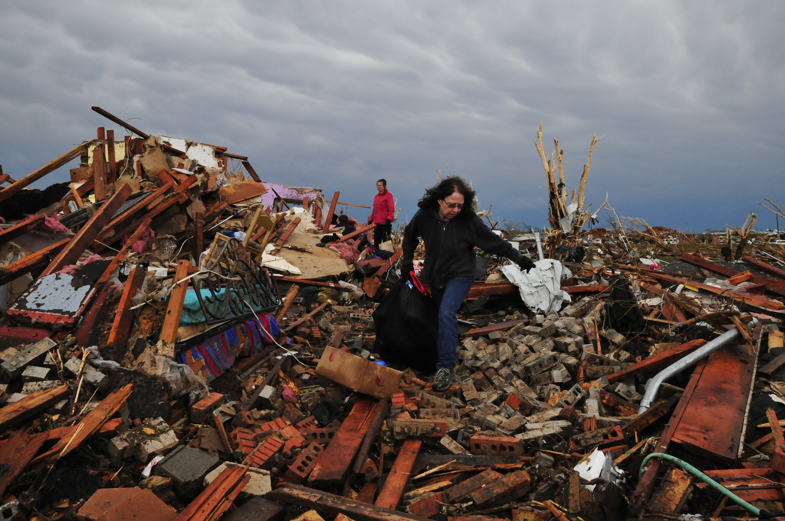 Debbie Mayhle, right, and her daughter Kristi Jones retrieve some of Debbie's belongings from her home which was in the direct path of yesterdays tornado on May, 21 in Moore Oklahoma.