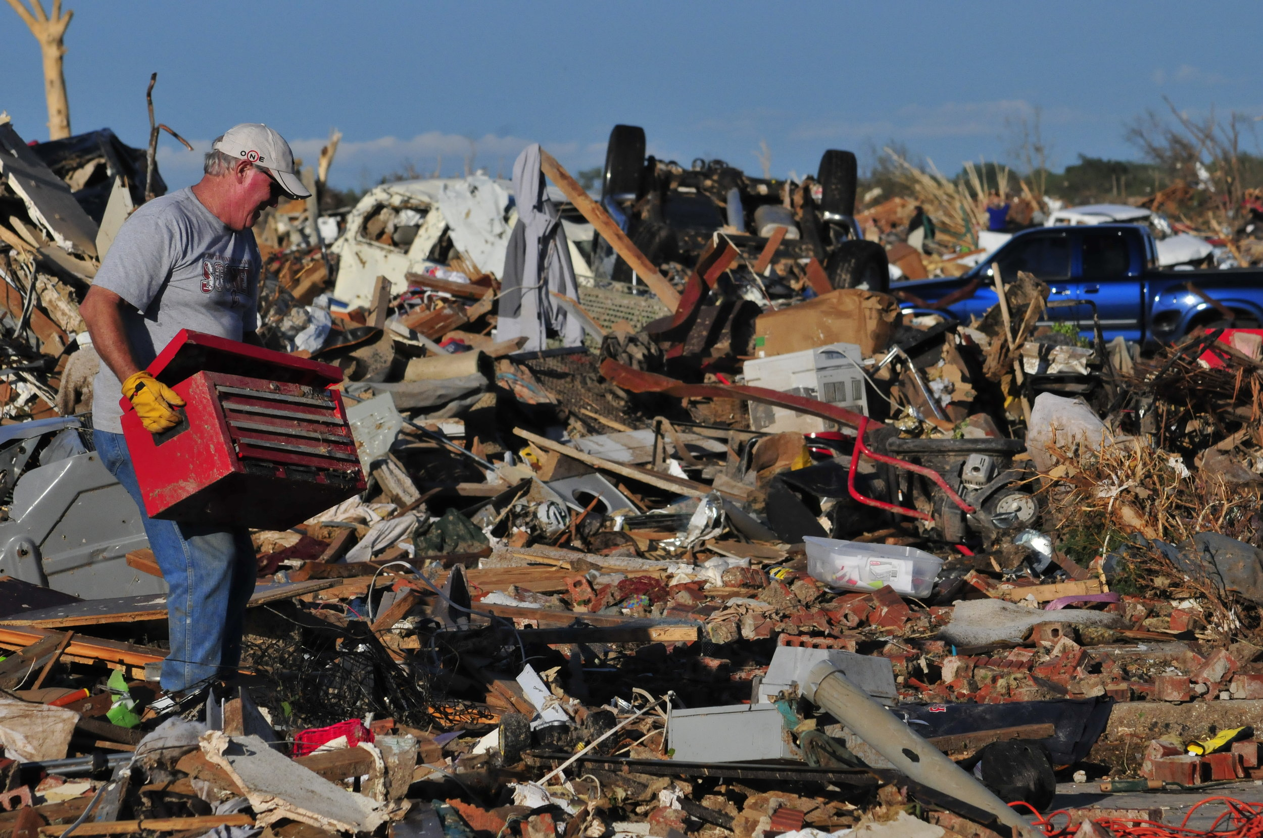 Robert Dixon removes a toolbox from his sons leveled home on May, 21 in Moore Oklahoma
