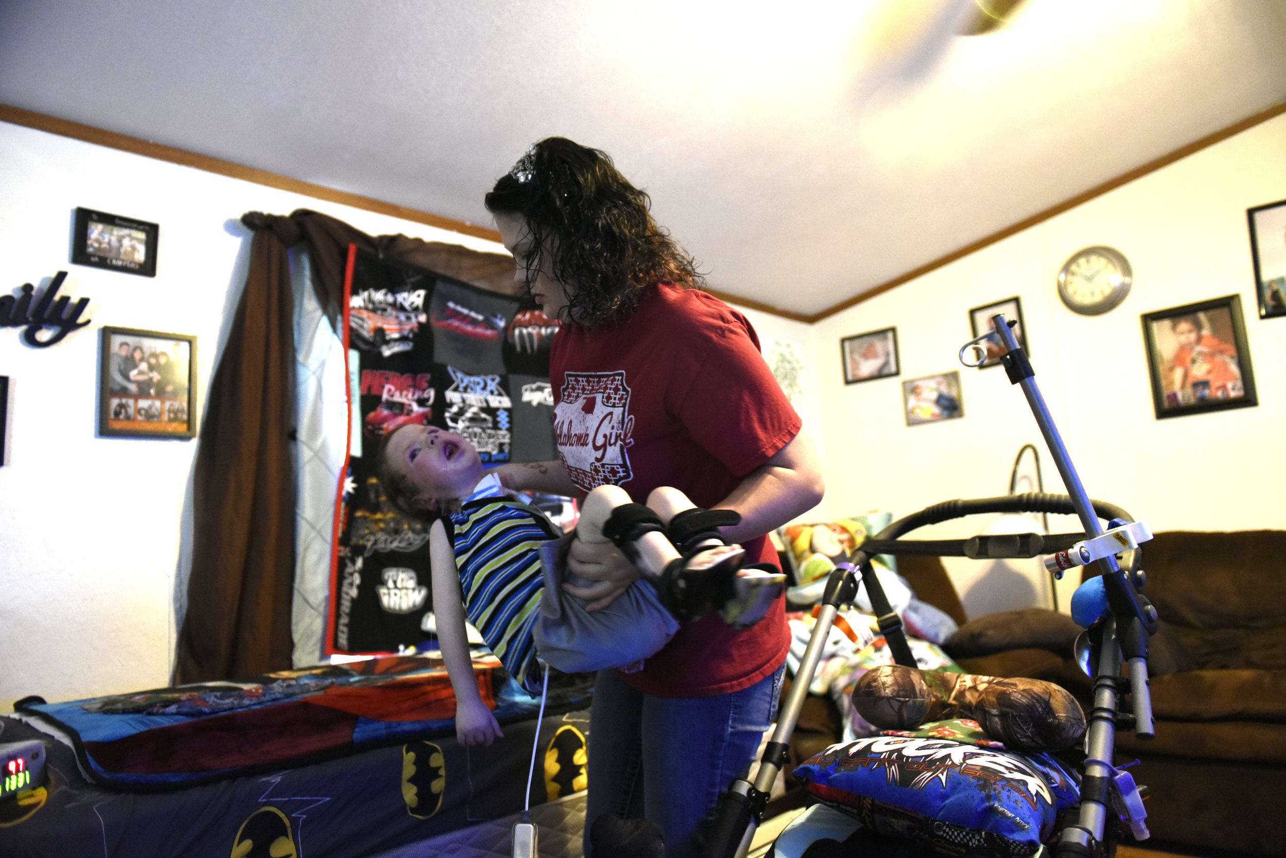Amanda Chaffin lifts her son Kayden, 4, who suffers from Spinal Muscular Atrophy at their home in Noble, Oklahoma. Chaffin is worried that cuts to medicaid at the state and national level will soon make the cost of caring for Kayden unaffordable for their family.