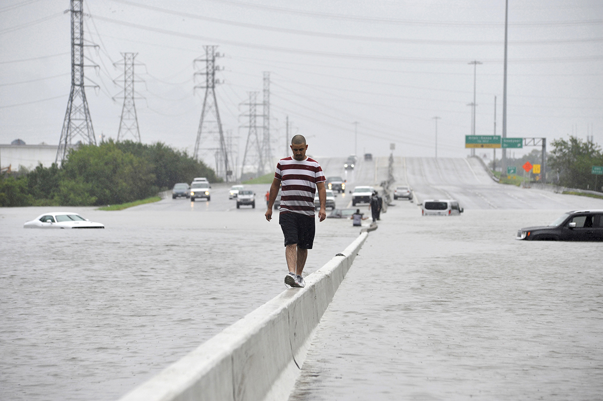 A stranded motorist escapes floodwaters on Interstate 225 after Hurricane Harvey inundated the Texas Gulf coast with rain causing mass flooding, in Houston, Texas, U.S. August 27, 2017.  REUTERS/Nick Oxford