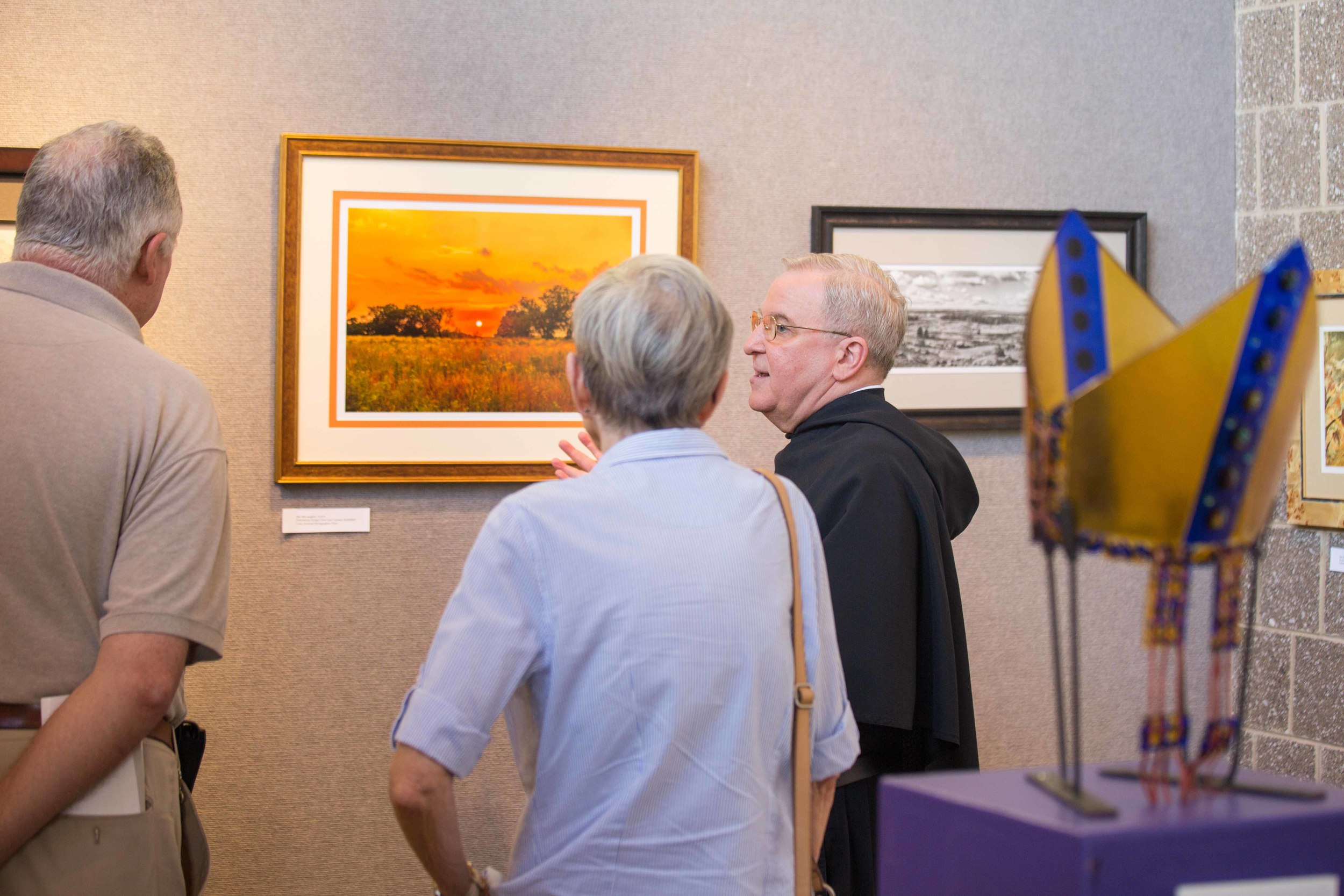 Father Dan McLaughlin, O.S.A., discusses his photograph with visitors to the art gallery in the Connelly Center