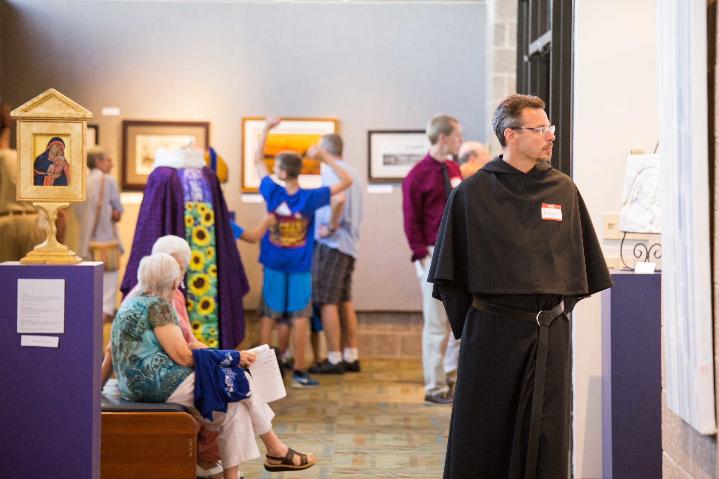 """Visitors to the Art Gallery during the """"A Day Celebrating Consecrated Life."""" At the left is an icon of the Madonna and a vestment, both done by Richard Canulli, O.S.A."""
