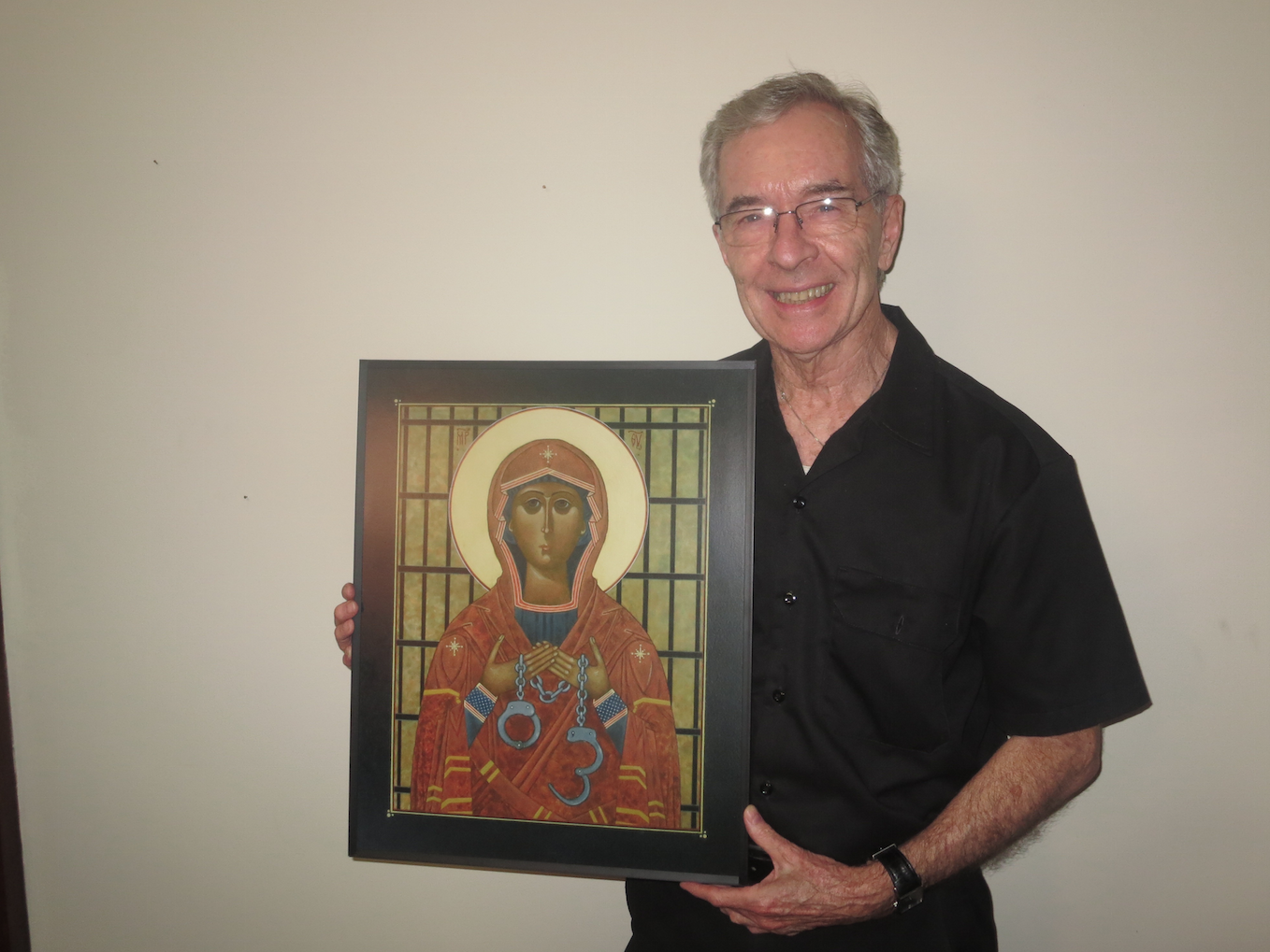 """Father Paul Morrissey, O.S.A., holding the icon, """"Mary, Mother of Captives."""""""