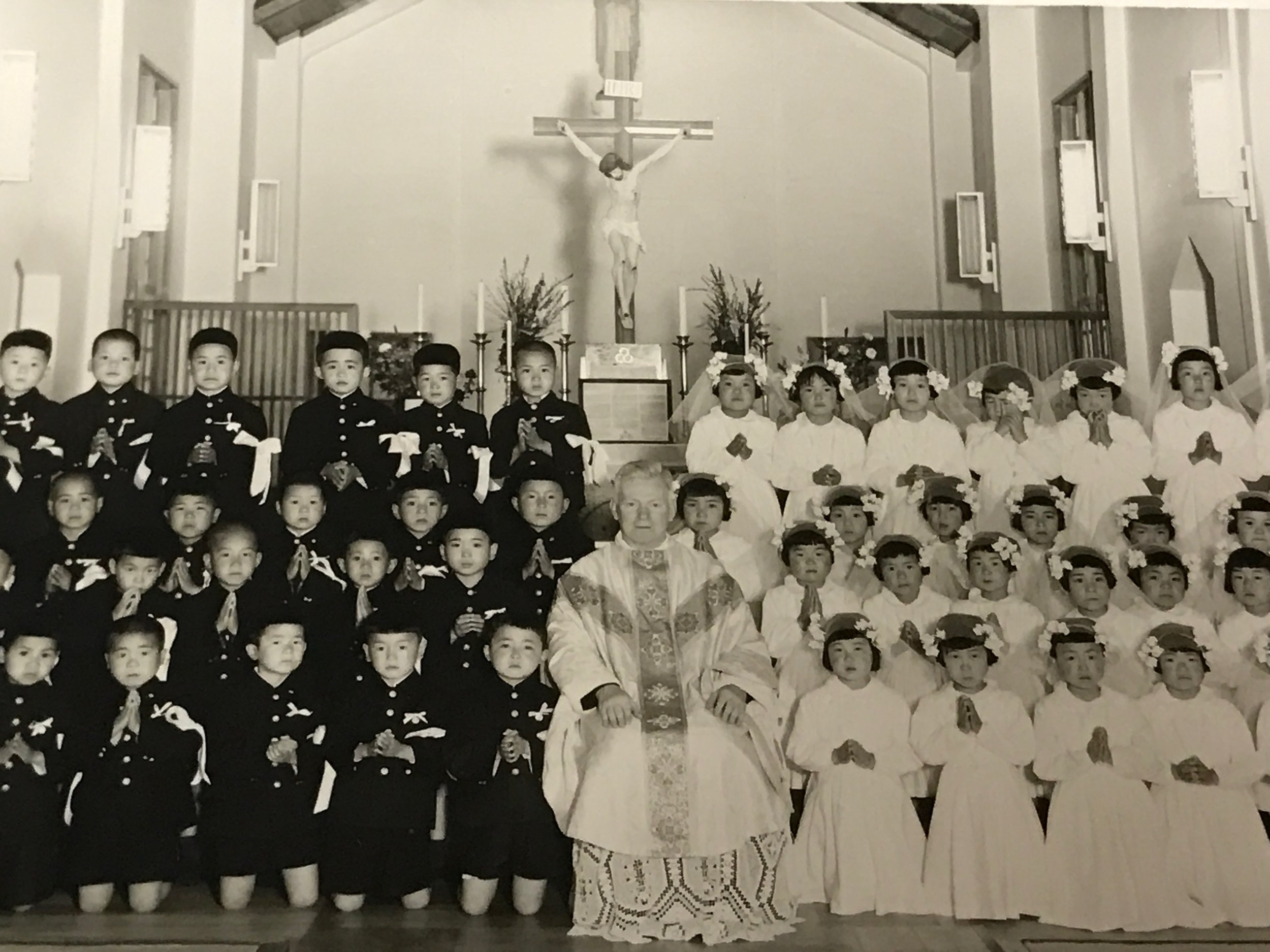 Father Purcell with Japanese children. Boys and girls were always seated on opposite sides of the church.