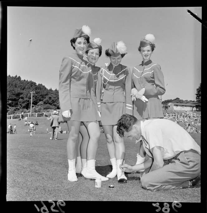 Four unidentified marching girls have their boots whitened by an unidentified man, 1956. National Library Archives.