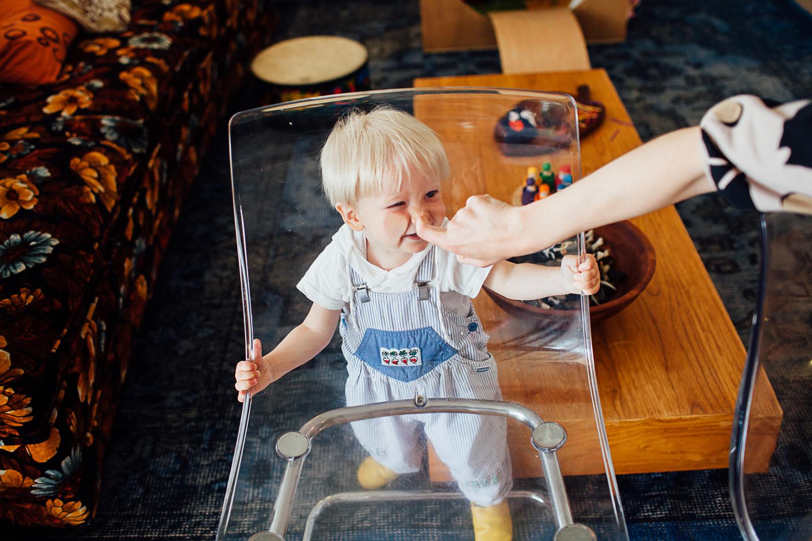 toddler faces through a transparent chair