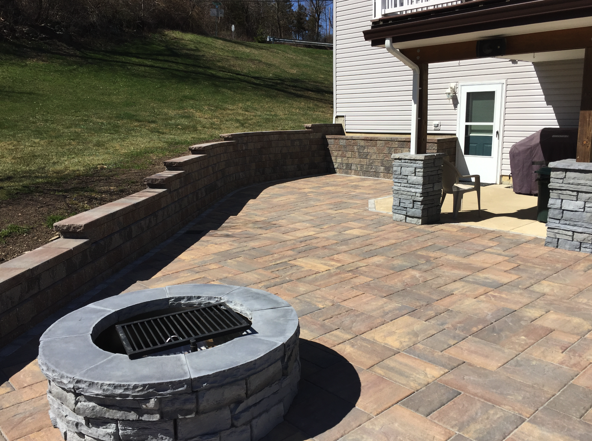 Patio Design in Dutchess County, NY with fire pit, retaining walls, and columns with overhead shade.