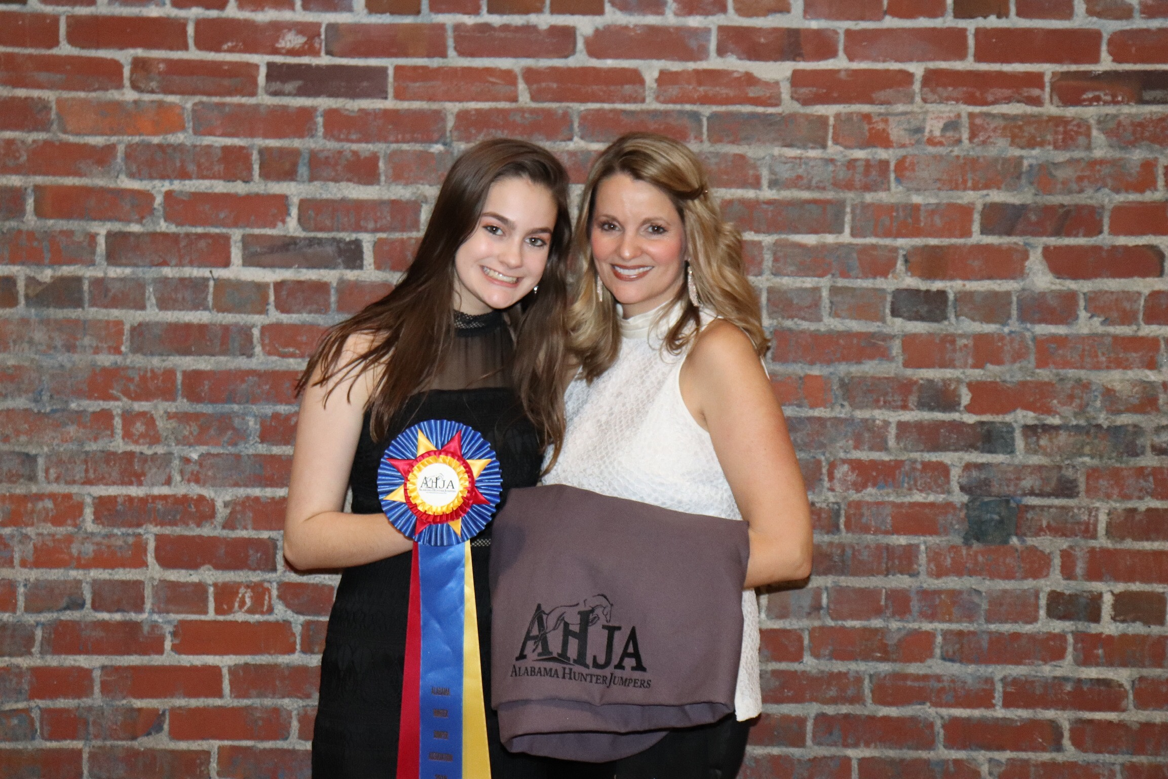 Campbell Swanner and mom Heather with Campbell's USEF High Point ribbon for the Children's Hunter division.