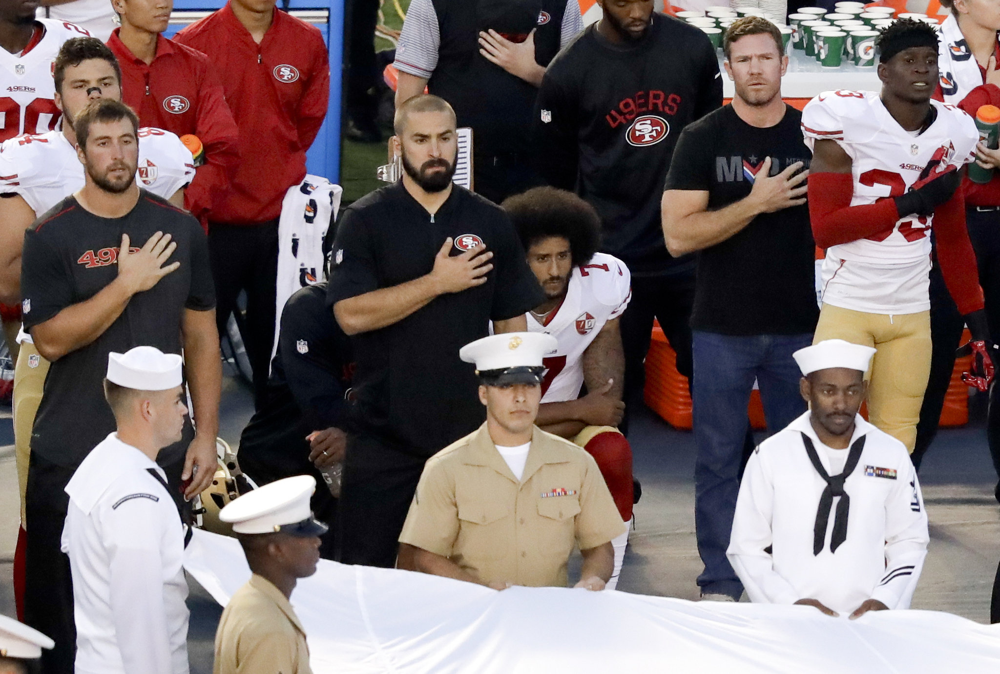 Colin Kaepernick, center,  sits during the national anthem