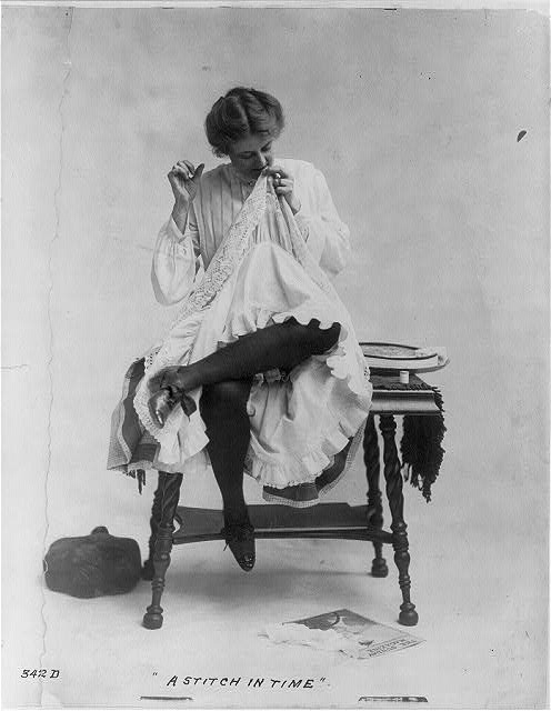 A-Stich-in-Time-Woman-seated-on-small-table-with-legs-crossed-mending-dress-which-she-is-wearing-ca.-1890-Library-of-Congress.jpg