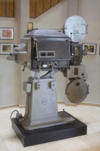 Old film projector of Esther Cinema, in Cinema Hotel, Tel Aviv. By:  idobi  (own work)  cc BY-SA3.0