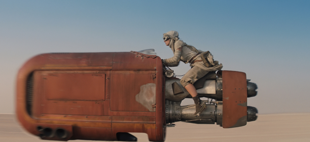 Rey, our orphaned heroine, not wearing pink and riding a hover thingy through the desert, much like Luke Skywalker once did.