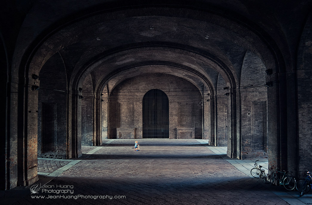 Child-on-Scooter-Swishing-through-Arches-of-War-Damaged-Palazzo-della-Pilotta-Parma-Italy-Copyright-Jean-Huang-Photography
