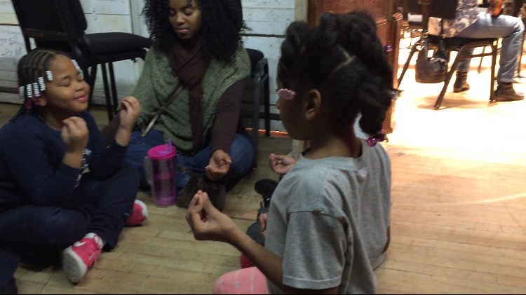 DAA Parent Kamilah meditating with our students in the wings of the DSO.