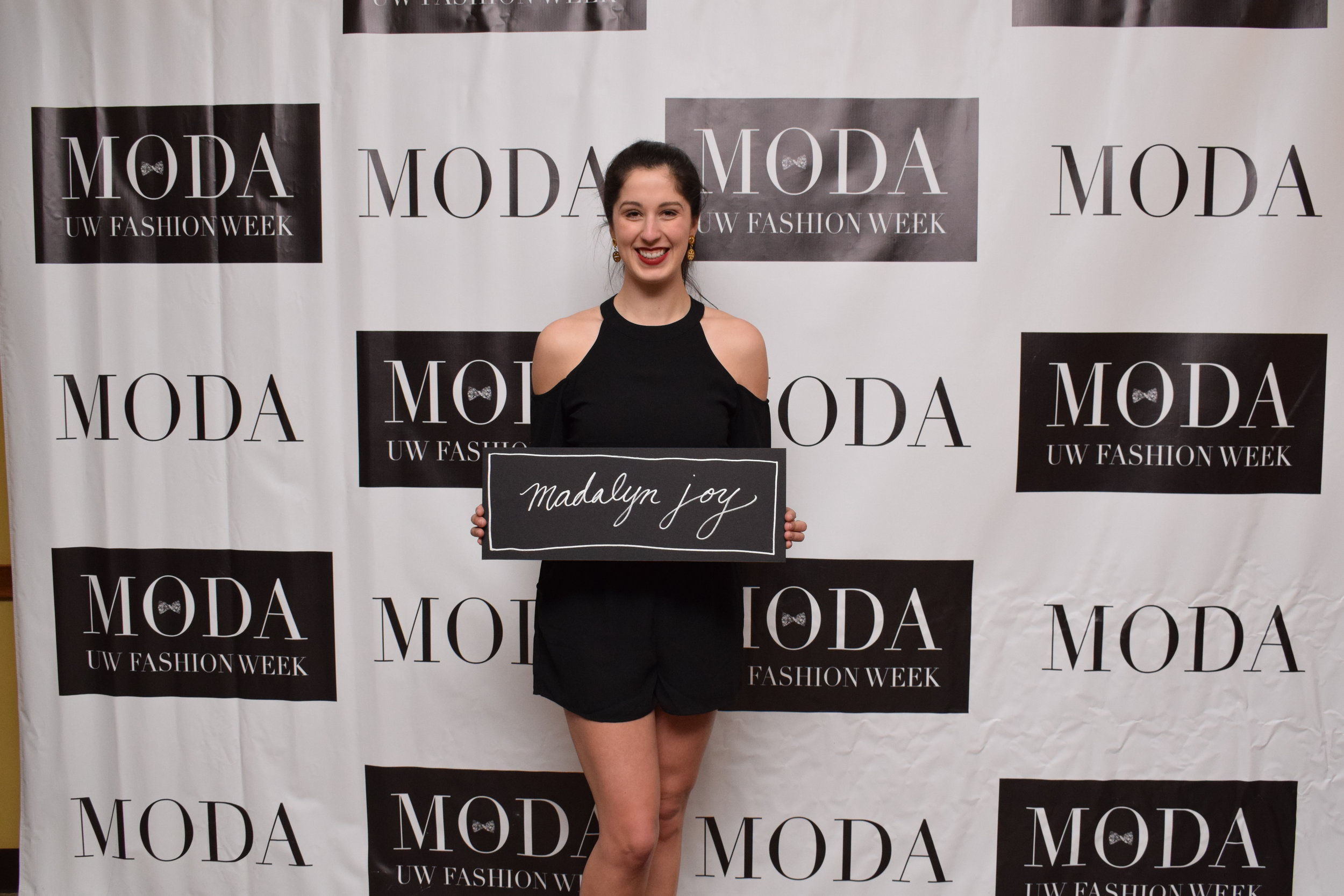 Madalyn posing in front of the Moda step and repeat before the show with her hand lettered sign by Emma Conklin.