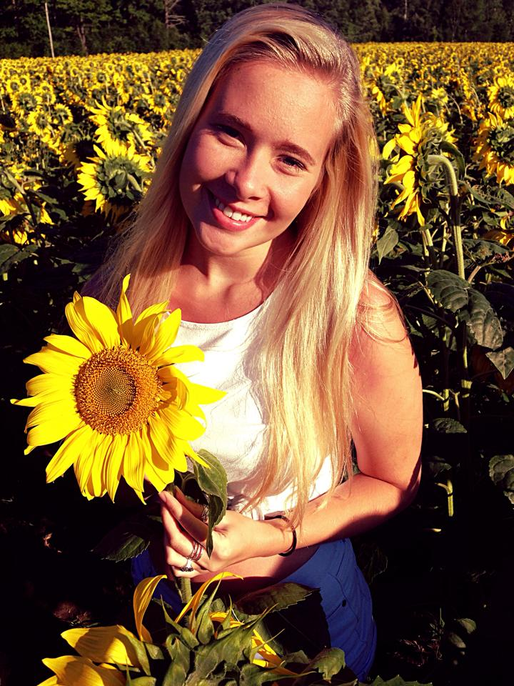 Claire posing with her favorite flower, sunflowers!