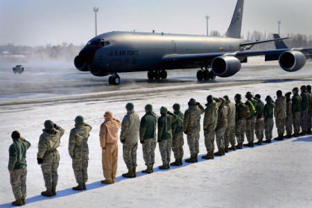 Airman salute the last KC-135 to fly combat mission from Manas taxis to park