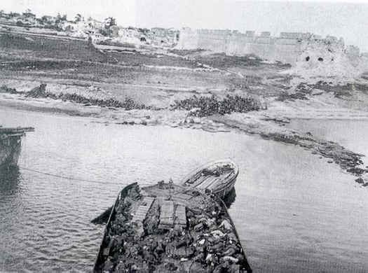 A photo taken from the deck of the River Clyde looking towards the shore of V beach. There are dead and wounded men in the lighter.