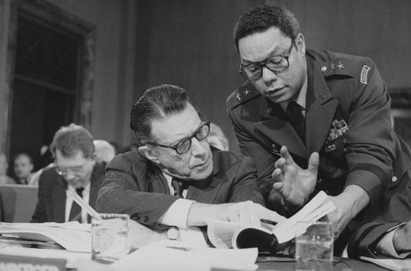 Defense Secretary Caspar Weinberger speaks with Army Maj. Gen. Colin Powell during testimony before the Senate Budget Committee on Capitol Hill on Feb. 8, 1985. (AP Photo)