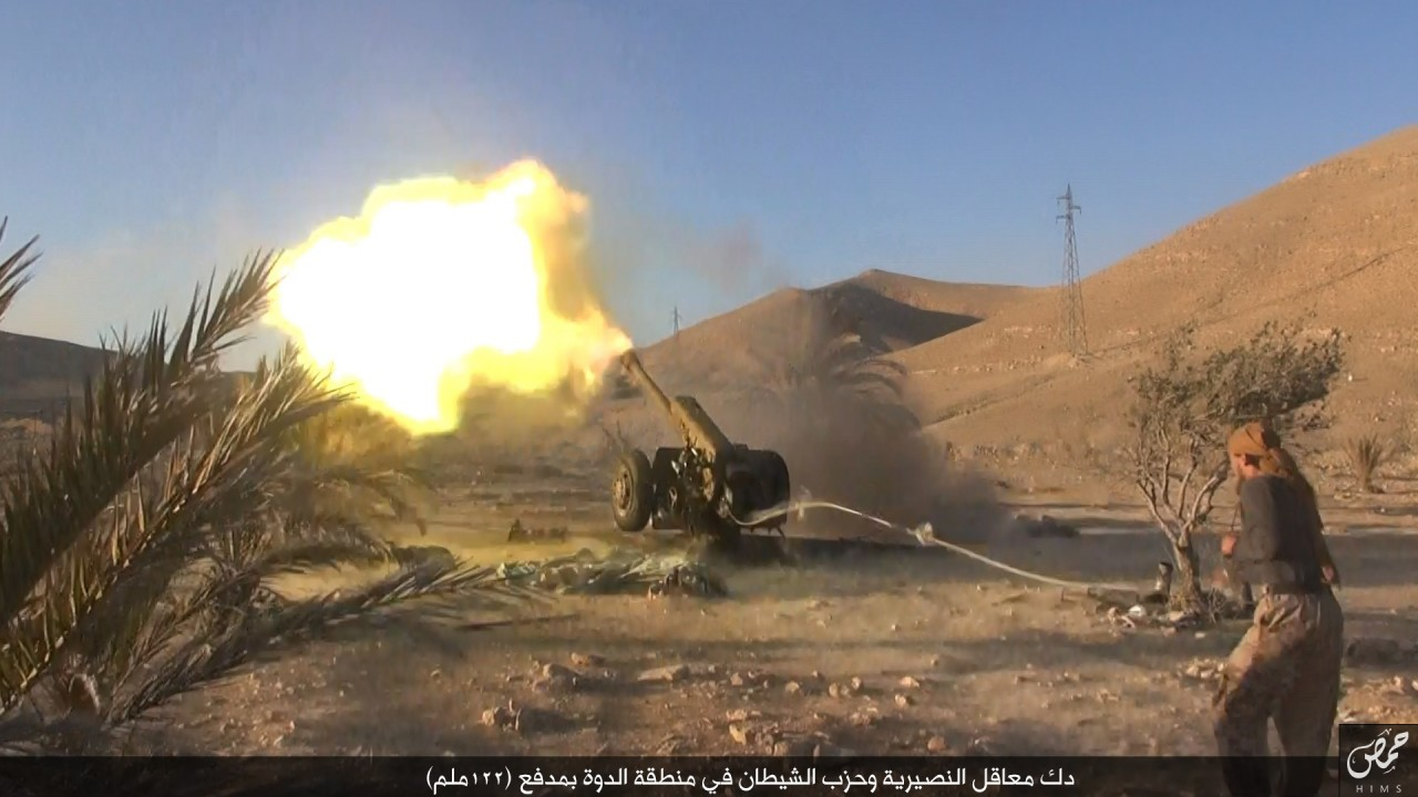 """""""Pounding  Nusayri  and  Hizb Al Shaytan  (party of Satan) bunkers in the  Ad Dawwah  region with a 122 mm cannon."""" Bottom right: Wilayah Homs Media Office logo."""