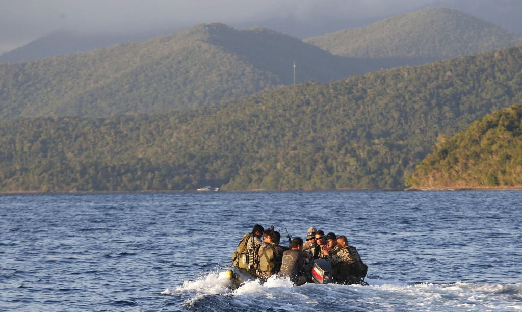 Members of the Philippine marines are transported on a rubber boat from a patrol ship after conducting a mission on the disputed Second Thomas Shoal, part of the Spratly Islands in the South China Sea, on their way to a camp in Palawan province, southwest Philippines, March 31, 2014. REUTERS/Erik De Castro