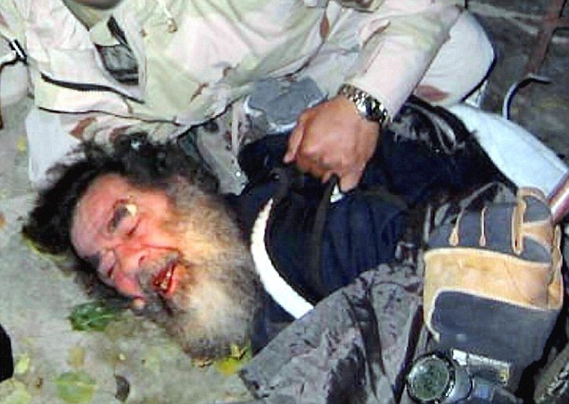 Saddam Hussein compelled to surrender by U.S. troops in December 2003.