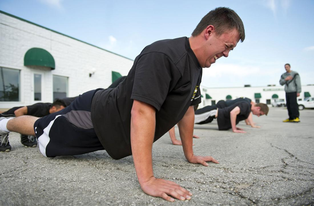 Kyle Bayard, 20, struggles to remain in position during a stationary push-up during physical exercise in the parking lot behind the Army recruiting station in Grandview, MO (Time.com)