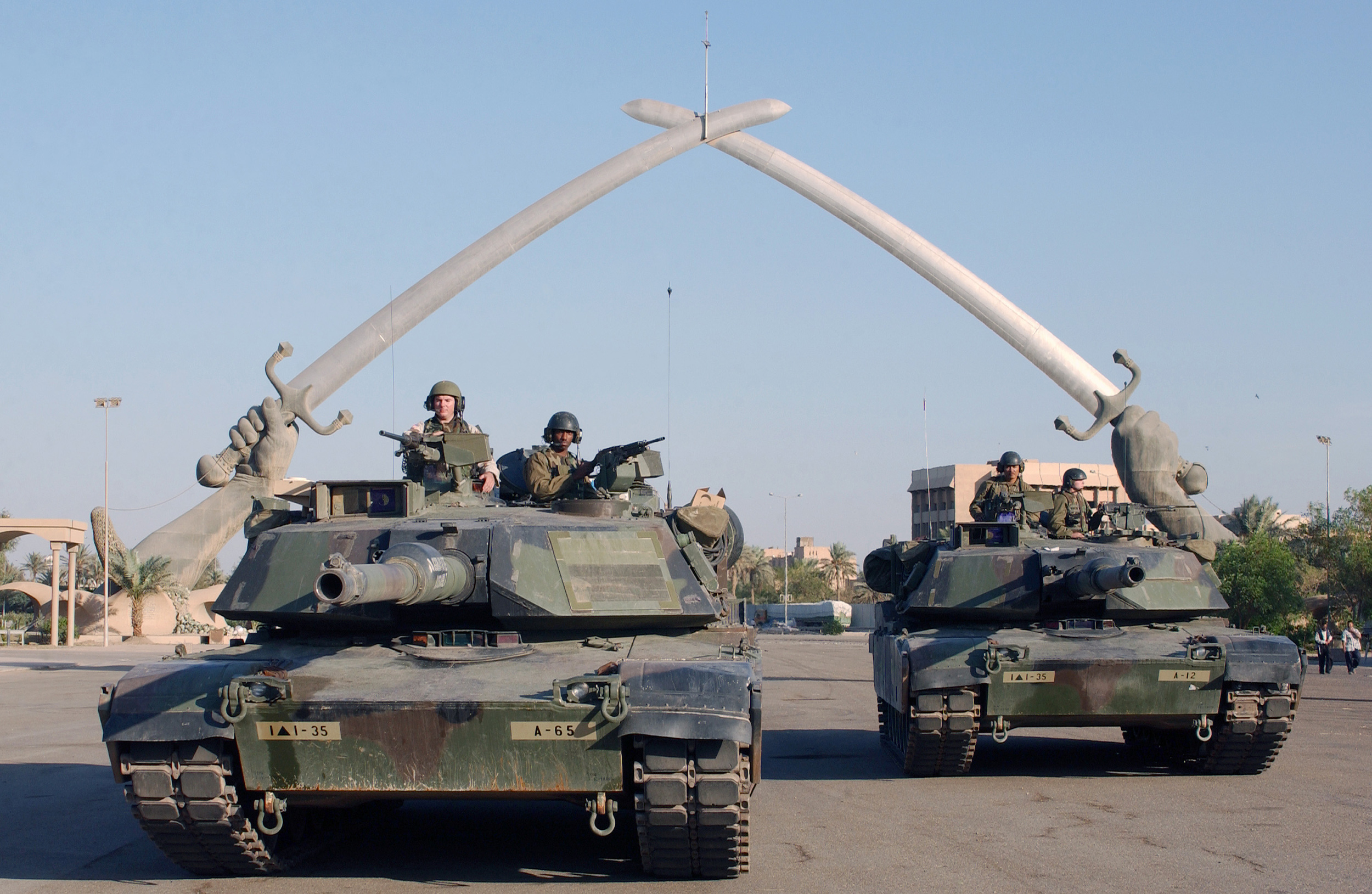 """M1A1 Abrams pose for a photo under the """"Hands of Victory"""" in Grand Festivities Square, Baghdad, Iraq 