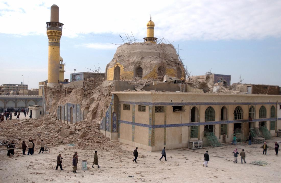 Iraqis walk past the damaged al-Askari mosque following an explosion in Samarra, 60 miles north of Baghdad, Iraq on Feb. 22, 2006. (Hameed Rasheed/AP)