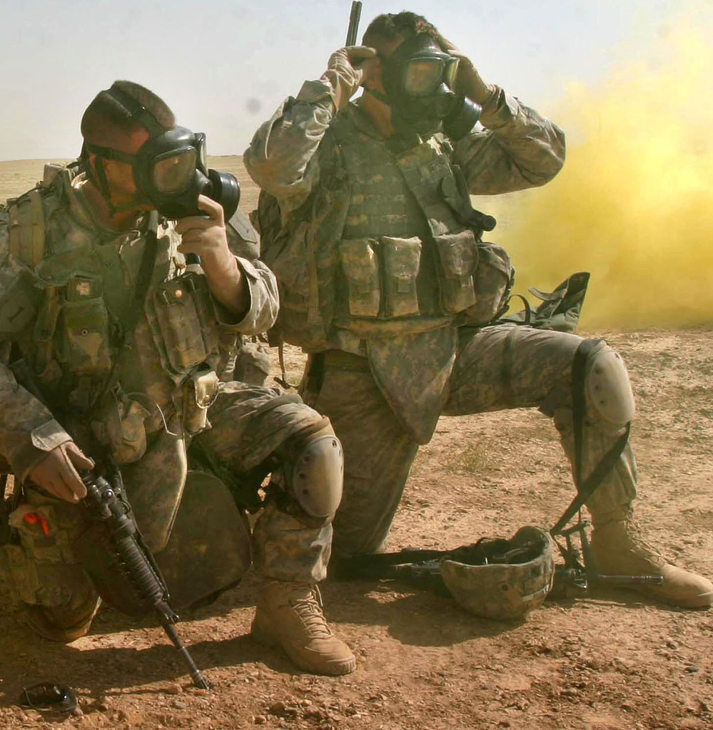 U.S. Army Soldiers put their gas masks on for a simulated chemical attack during a training mission near Camp Ramadi, Iraq, Sept. 25, 2007. ( U.S. Marine Corps photo )