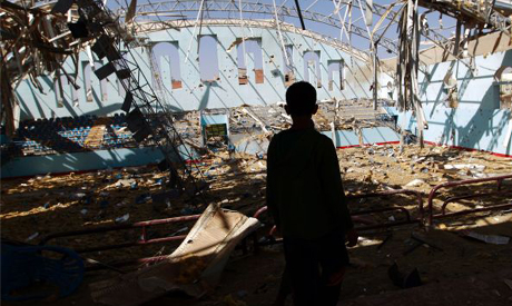 A Yemeni boy inspect the damage at a sports hall that was partially destroyed by Saudi-led air strikes in the Yemeni capital Sanaa on January 19, 2016 ( AFP )