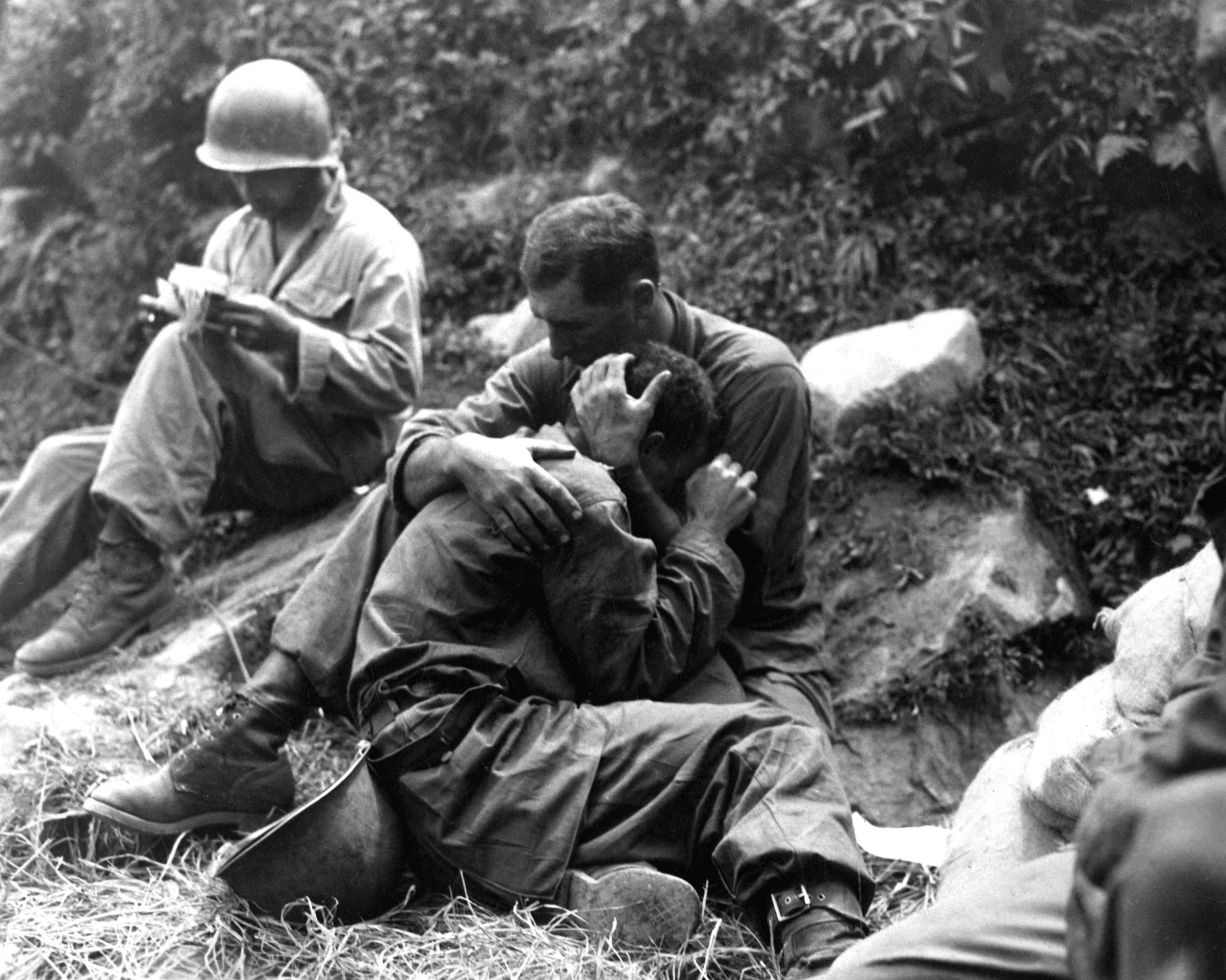 A grief stricken American infantryman whose friend has been killed in action is comforted by another soldier. In the background a corpsman methodically fills out casualty tags. Sfc. (SFC Al Chang/U.S. Army Photo)