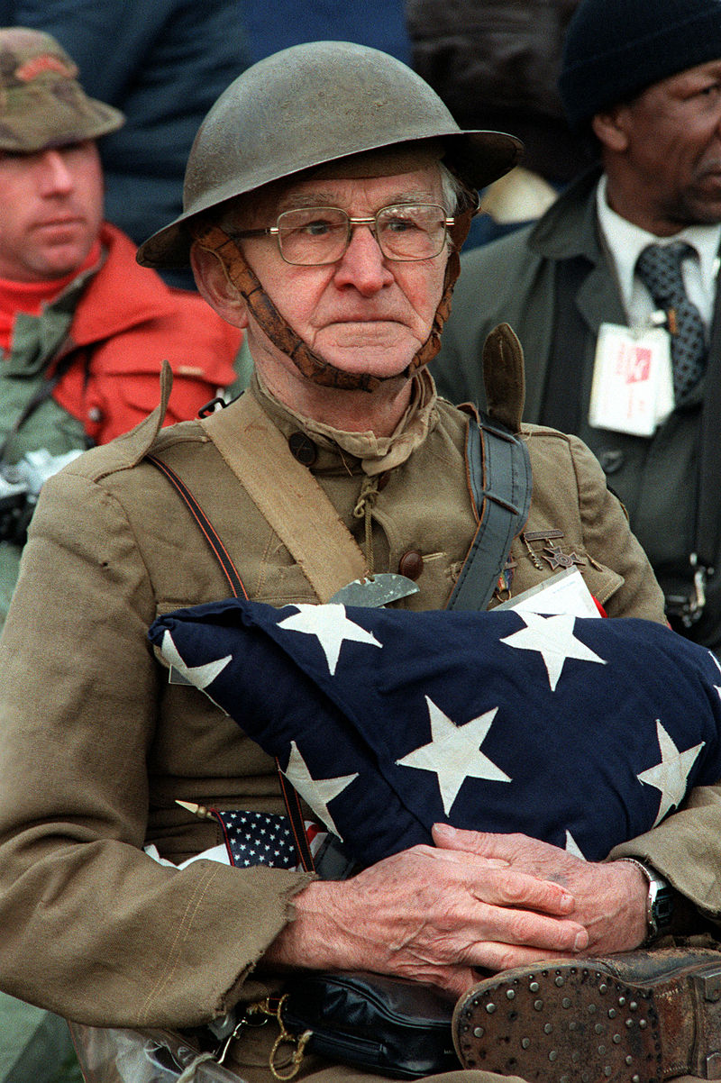 Joseph Ambrose, a World War I veteran, at the dedication for the Vietnam Veterans Memorial. He is holding the flag that covered the casket of his son,killed in the Korean War. (Mickey Sanborn/DOD Photo)
