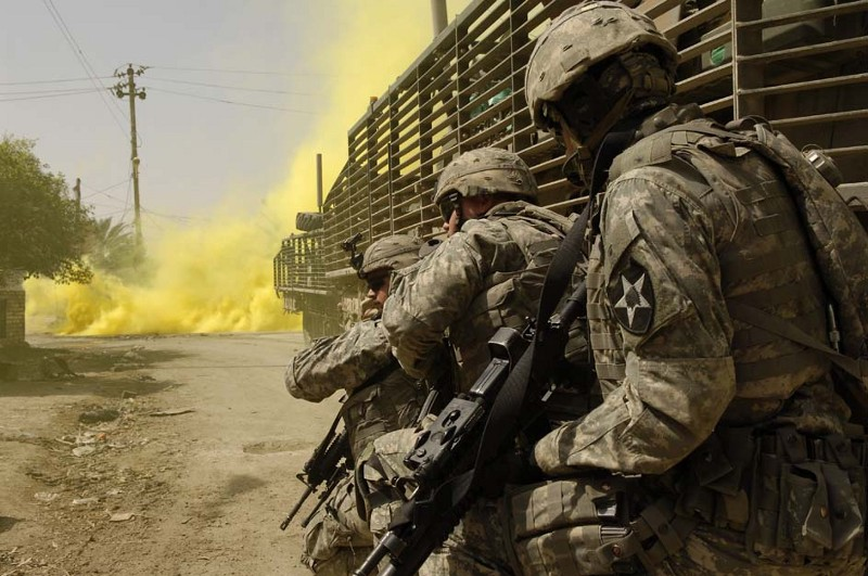 Soldiers take cover behind a Stryker vehicle during a firefight (Wikimedia)