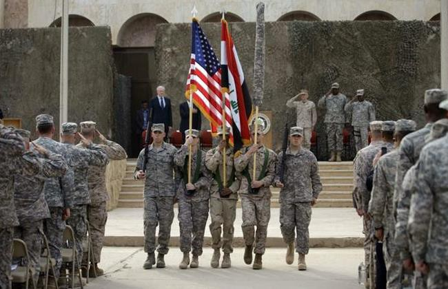 US and Iraq flag and the US Forces-Iraq colors are carried during ceremonies marking the end of US military mission in Baghdad, Iraq (Khalid Mohammed/AP)