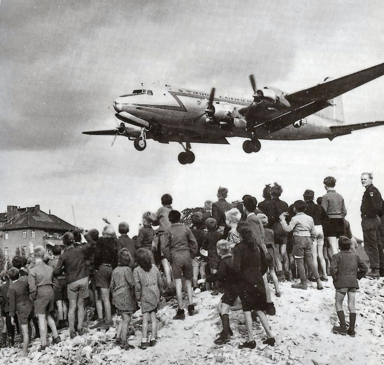 Berliners watch a Douglas C-54 Skymaster land at Tempelhof Airport, 1948 ( Wikimedia Commons )